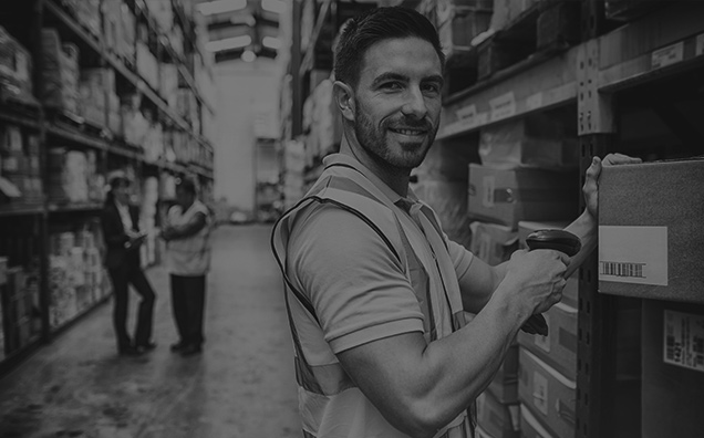 black and white image of man wearing a high-vis in warehouse smiling at camera and scanning a box